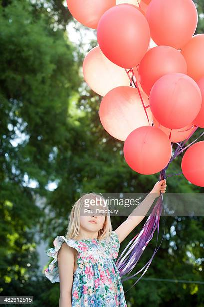Young girl outdoors holding balloons
