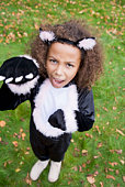 Young girl outdoors in cat costume on Halloween