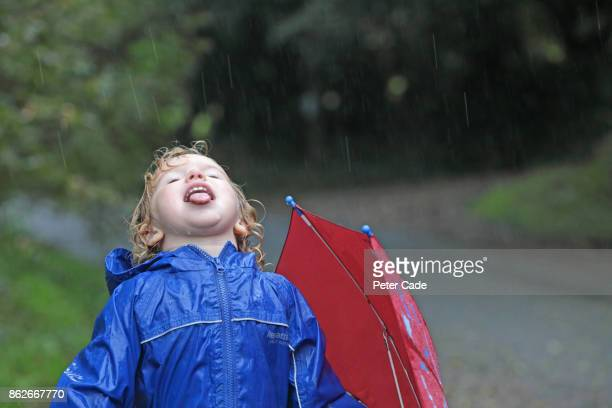 Young girl outside catching rain on her tongue