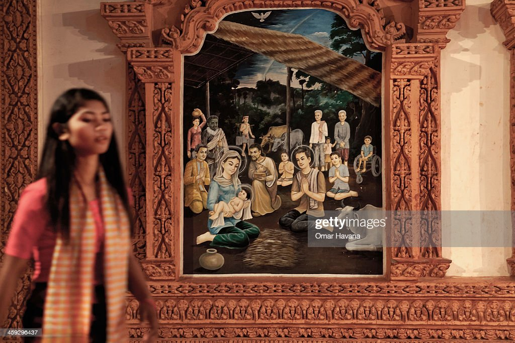 A young girl passes in front of a painting of the Nativity in the church of Tahen village during the Christmas Eve celebrations on December 24, 2013 in Battambang, Cambodia. The parish at Battambang dates back to 1790 when the Catholic community first arrived. Now they serve around 1000 Catholics and 600 families.