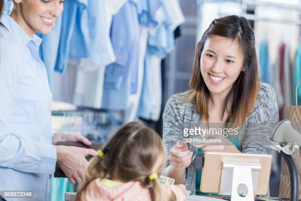 Young girl pays for purchase in clothing store