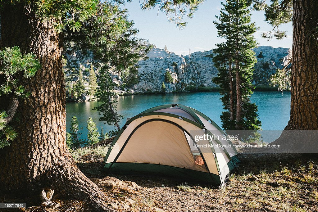 Young girl peeking from camp tent by alpine lake : Stock Photo