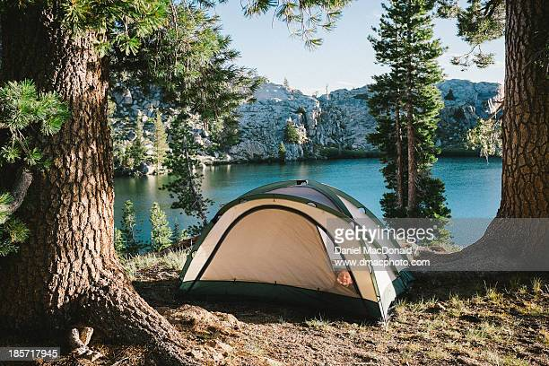 Young girl peeking from camp tent by alpine lake