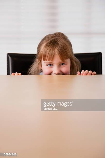 Young girl peeking out from behind table