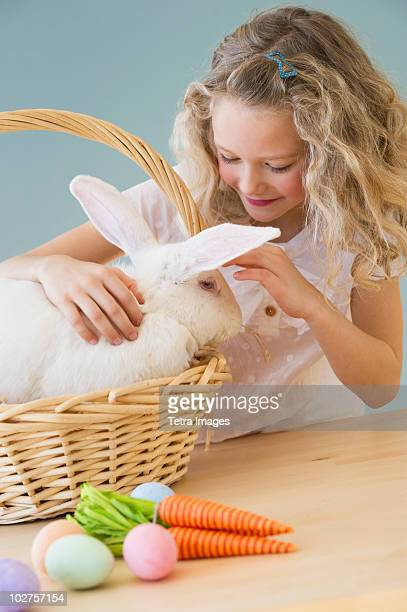 Young girl petting a rabbit in a basket