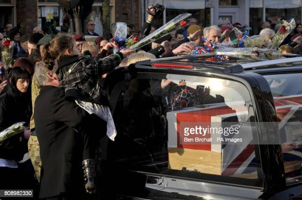 A young girl places a single red rose on top of the hearse containing the Union Flag draped coffin of Corporal Stephen McKee of the Royal Irish...