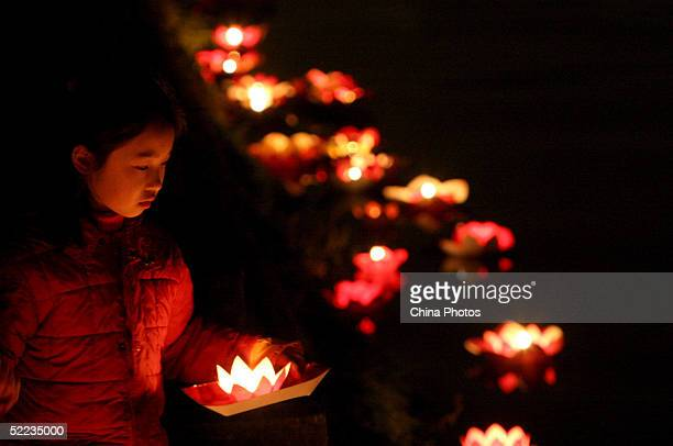 A young girl places candlelights into a river during a ceremony to mark the lantern festival on February 23 2005 in Chengdu of Sichuan Province China...