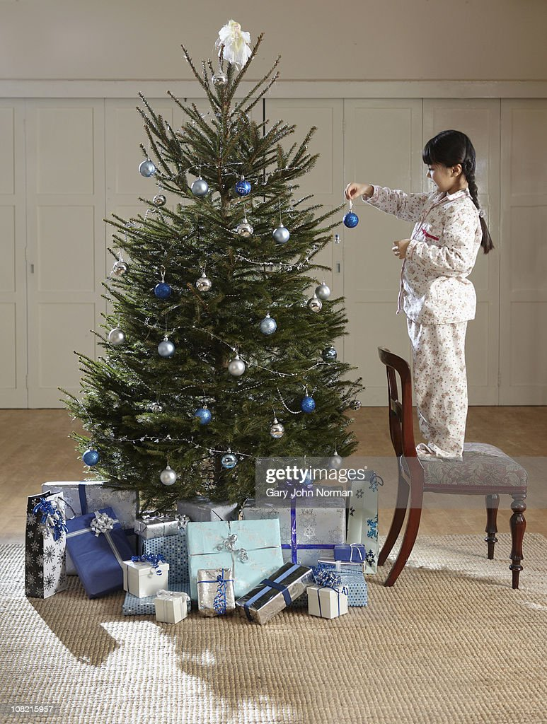 Young girl places decoration on tree : Stock Photo