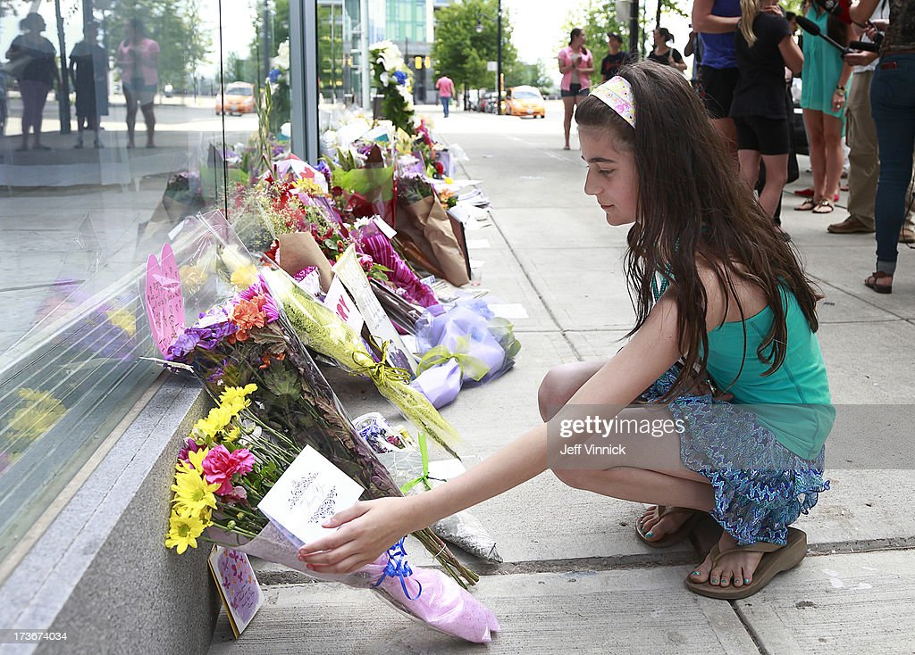 A young girl places flowers on a memorial to deceased actor Cory Monteith outside the Fairmont Pacific Rim Hotel on July 16, 2013 in Vancouver, British Columbia, Canada. The B.C. Coroners Service released results of Monteith's autopsy today and found the 31-year-old's cause of death was a mixed drug toxicity involving heroin and alcohol.