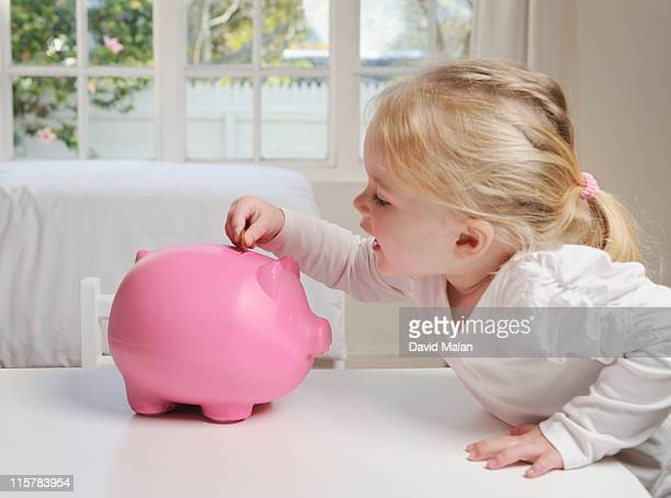 Young girl placing a coin in a piggy bank.