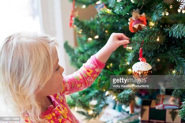Young girl placing ornament on Christmas tree.