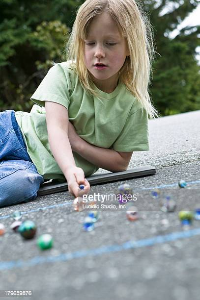 Young girl playing a game of marbles