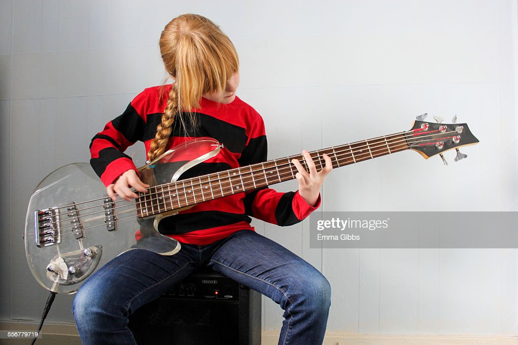 Young girl playing electric guitar