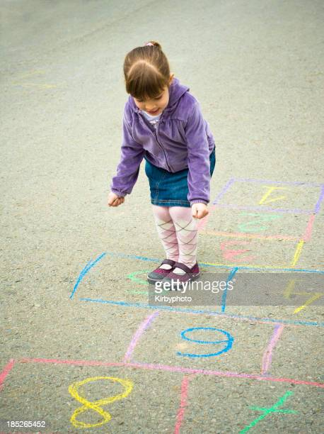 A young girl playing hopscotch by herself on the sidewalk