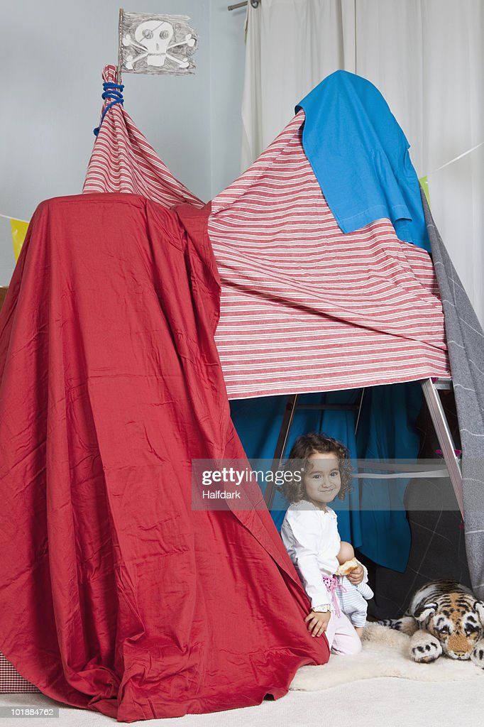 A young girl playing in a fort : Stock Photo