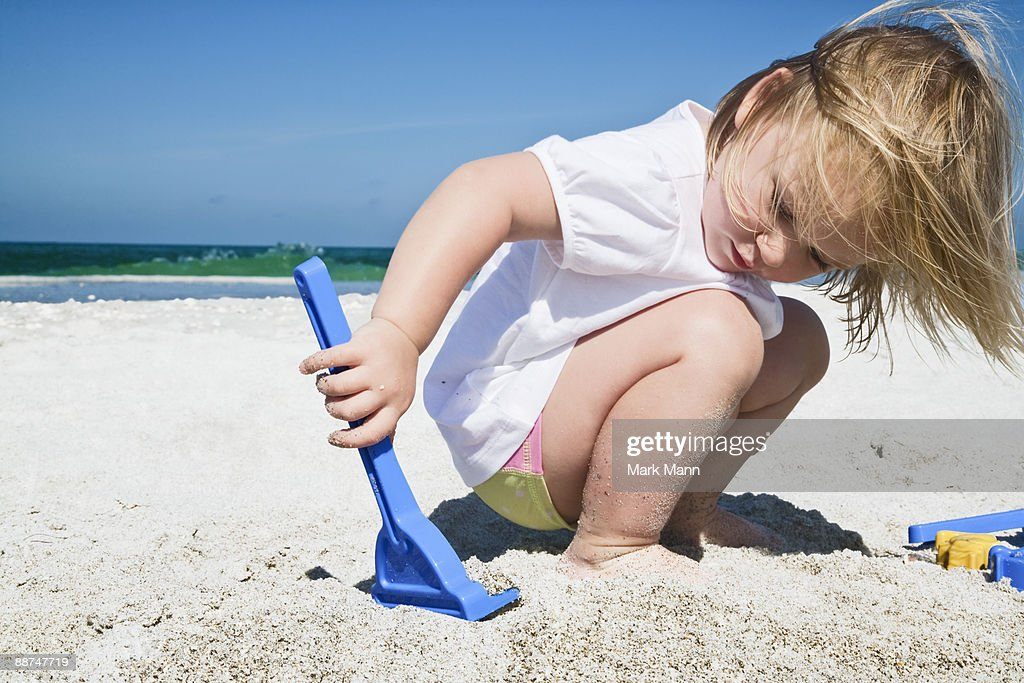 Young girl playing in the sand. : Stock Photo