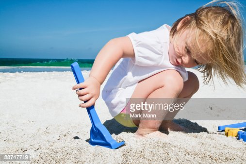 Young girl playing in the sand. : ストックフォト