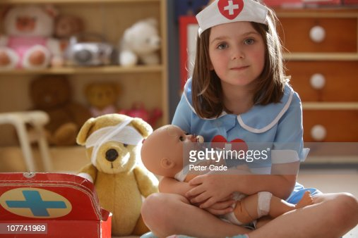 young girl playing nurse with her toys : Stock Photo