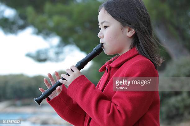 Young girl playing recorder by the beach.