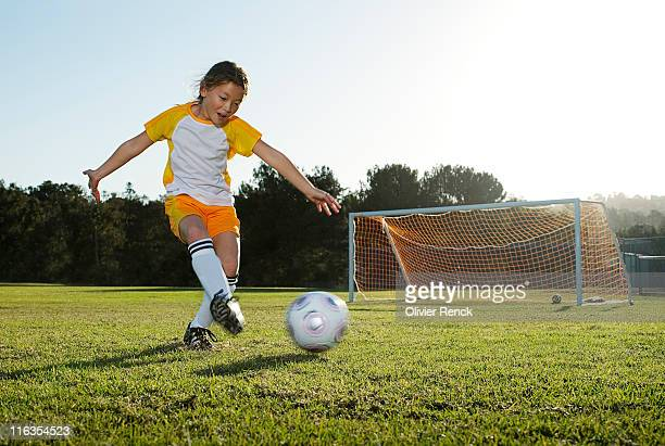 A young girl playing soccer on a soccer field in Los Angeles, California.