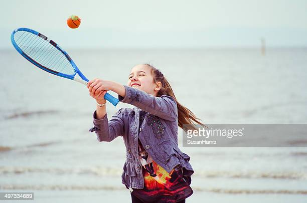 Young girl (12-13) playing tennis