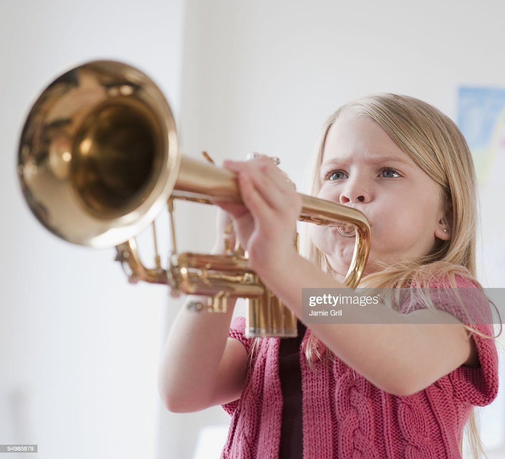 Young girl playing the trumpet : Stock Photo