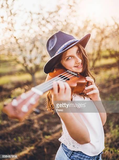 Young girl playing ukulele