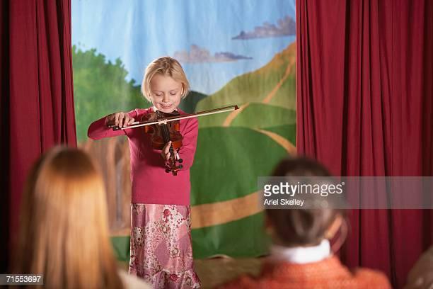 Young girl playing violin at recital