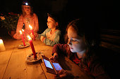 A young girl playing with a batterypowered Nintendo computer game during a power cut at a house in Capel Curig in north Wales The electricity supply...