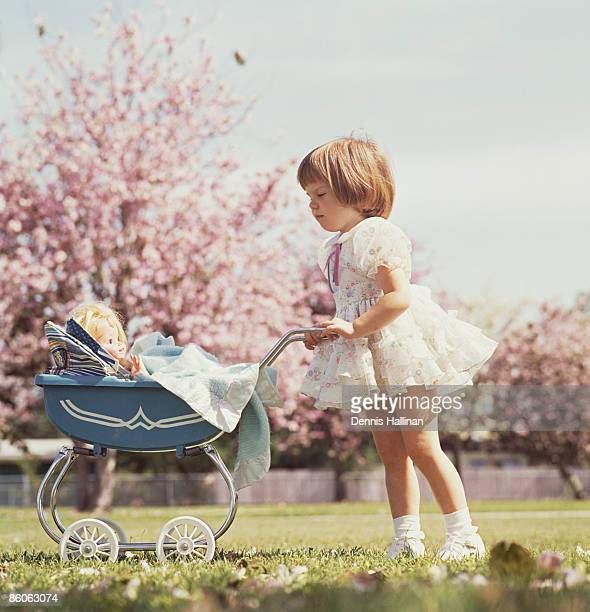 Young girl playing with baby doll pushing carriage