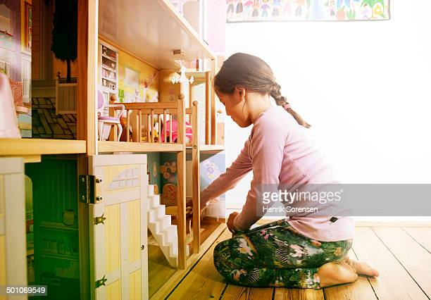 young girl playing with dollhouse