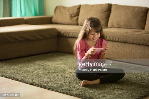 Young girl playing with smartphone in living room : Stock Photo