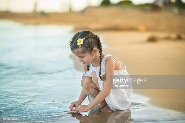 Young girl playing with starfish on tropical beach