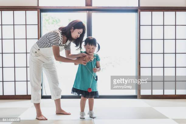 Young girl playing with toy at home with her mother