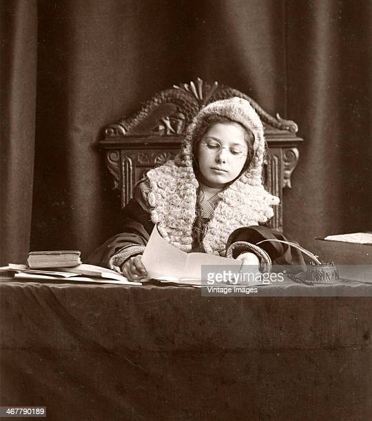 A young girl plays at being a judge circa 1910