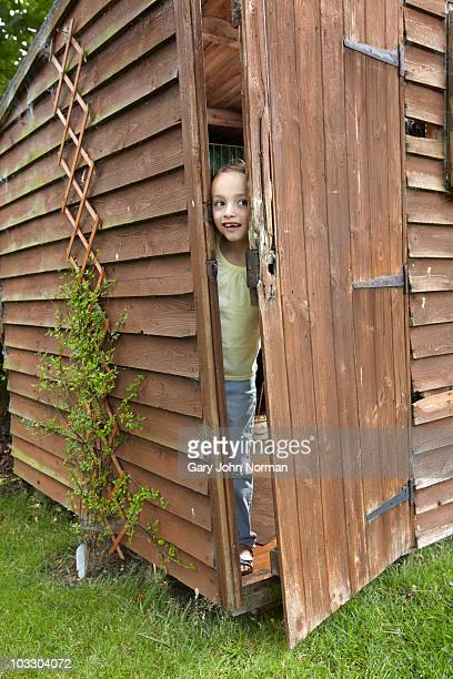 Young girl plays hide and seek in garden