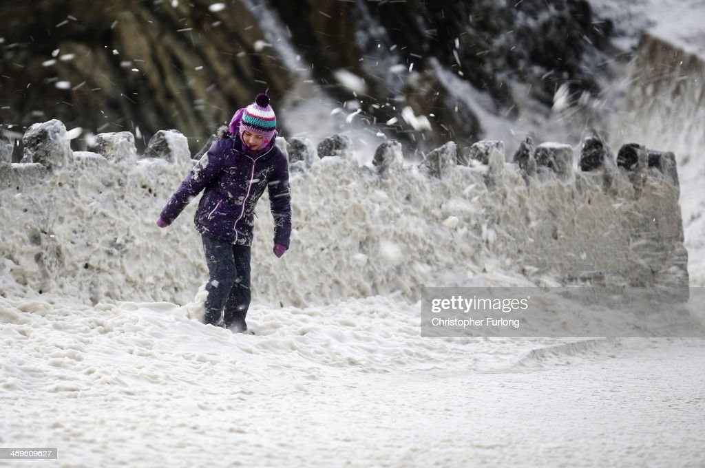 A young girl plays in a blizzard of sea foam whipped up by the wind near Trearddur Bay on December 27, 2013 in Anglesey, United Kingdom. A yellow 'be aware' warning has been issued for many parts of Britain as the country is affected by gale force winds and heavy rain.