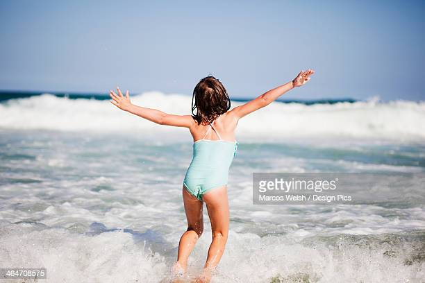 A Young Girl Plays In The Waves Of The Ocean
