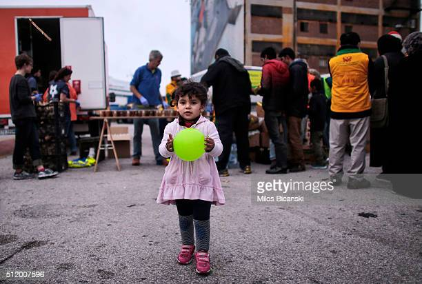 A young girl plays with a balloon as migrants wait for their turn at a food distribution stand run by a humanitarian aid charity after arriving from...
