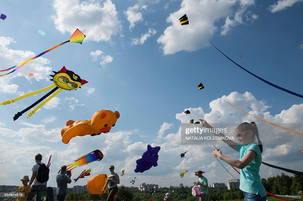 A young girl plays with a kite during the 'speckled sky' festival in Moscow, on May 28, 2016. / AFP / NATALIA