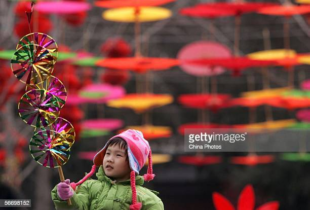A young girl plays with a pinwheel during a temple fair at the Temple of Earth for Chinese New Year celebrations January 29 2006 in Beijing China...