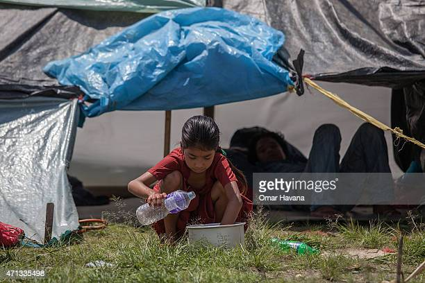 A young girl plays with a plastic bottle in an evacuation area set up by the authorities in Tundhikel park on April 27 2015 in Kathmandu Nepal A...