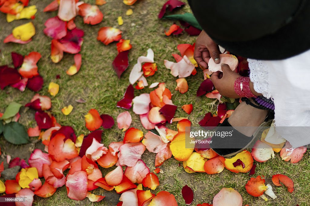 "A young girl plays with colorful rose petals during the Inti Raymi celebration on 26 June 2010 in the village of Pesillo, Ecuador. Inti Raymi, ""Festival of the Sun"" in Quechua language, is an ancient spiritual ceremony held in the Indian regions of the Andes, mainly in Ecuador and Peru. The lively celebration, set by the winter solstice, goes on for various days. The highland Indians, wearing beautiful costumes, dance, drink and sing with no rest. Colorful processions in honor of the God Inti (Sun) pass through the mountain villages giving thanks for the harvest and expressing their deep relation to the Mother Earth (Pachamama)."