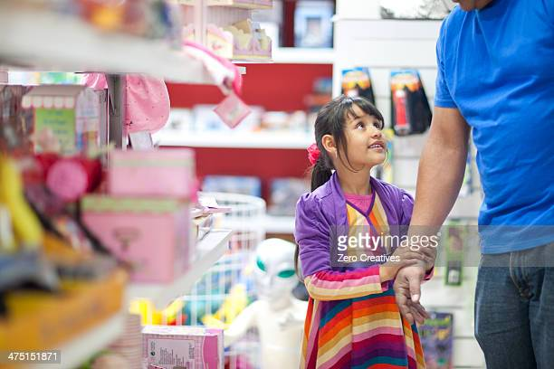 Young girl pleading with father in toy shop