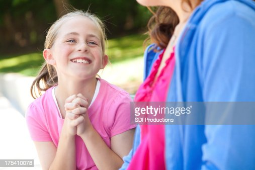 Young girl pleading with her mother for something