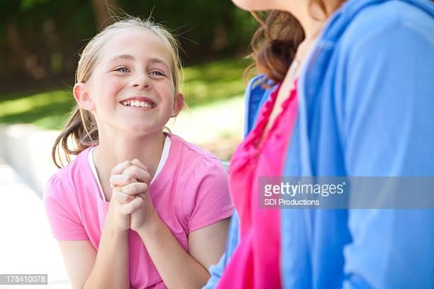 Giovane ragazza con la madre che chiede qualcosa