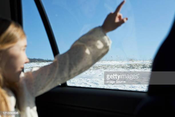 Junges Mädchen zeigt durch ein Fenster