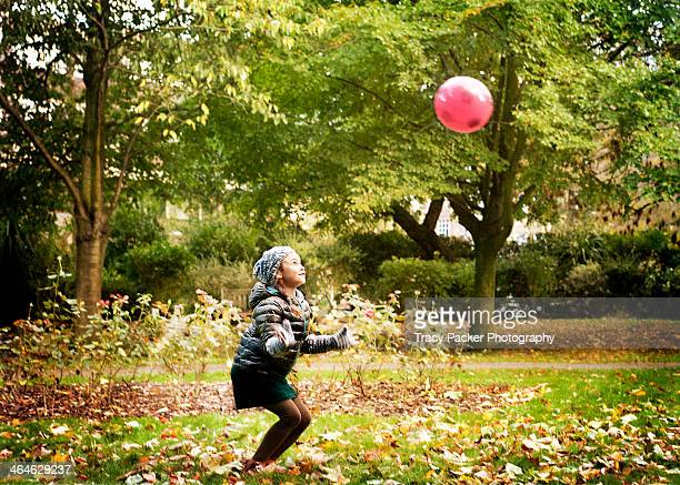 Young girl poised to catch a ball in a London park