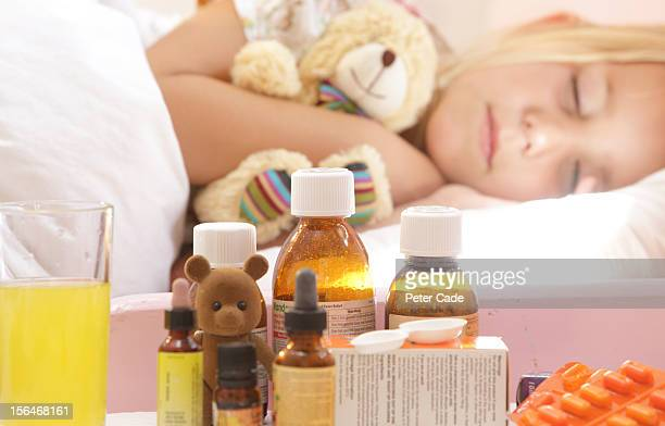 Young girl poorly in bed with medication on table