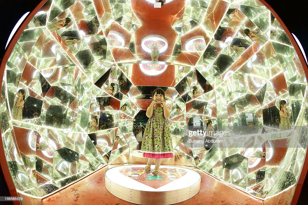 A young girl pose for a photo inside a 3m tall walk-in kaleidoscope on Orchard Road on November 17, 2012 in Singapore. Every year, the famous shopping belt comes aglow with festive decorations and attracts thousands of visitors. Themed 'Christmas on A Great Street', the annual event will run till January 6, 2013.